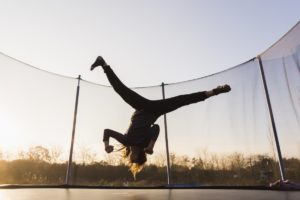 young woman jumping upside down in a big trampoline outdoors
