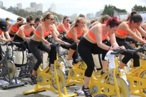 a group of women doing cycling training together in a team-based workout class outdoors