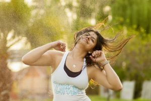 energetic young woman smiling and dancing zumba outdoors
