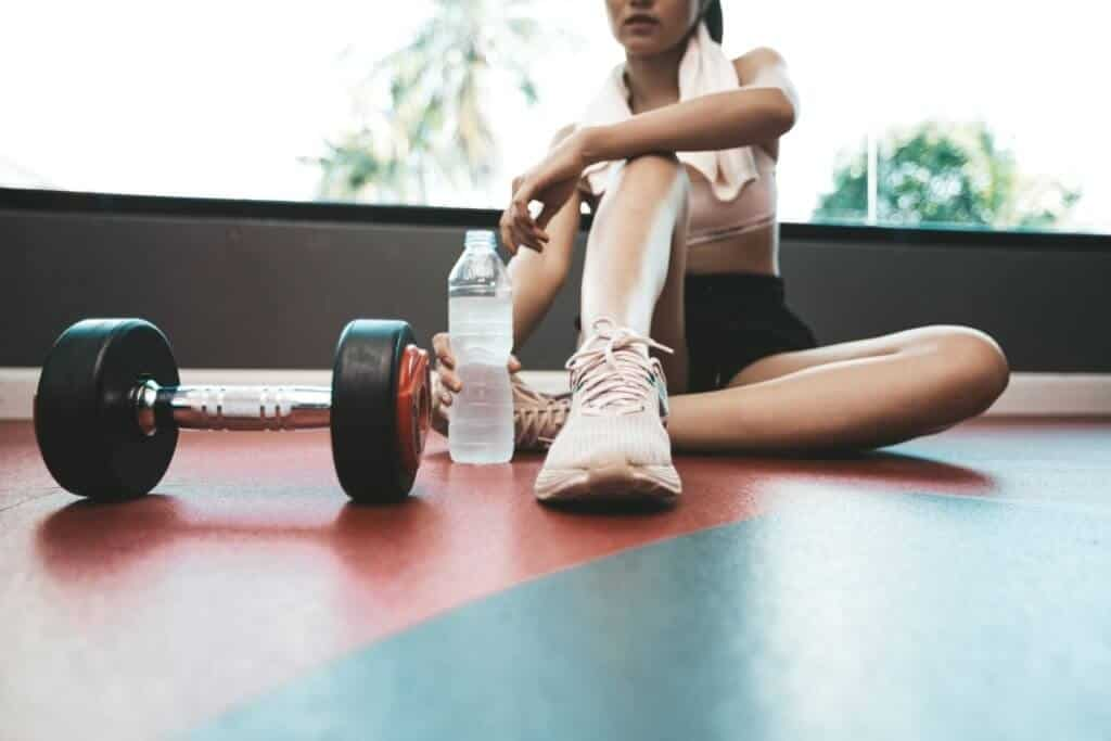 girl sitting down with a water bottle in her hand at the gym Trendy Workout Exercises to Try